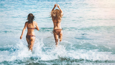 A photo of two women running towards the sea